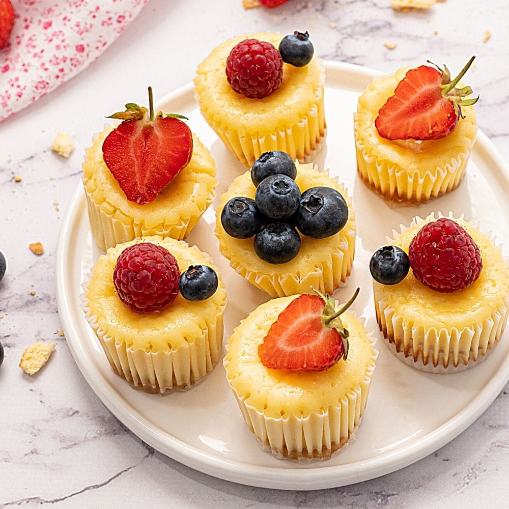 Mini Muffin tin cheesecakes on white platter topped with fresh berries