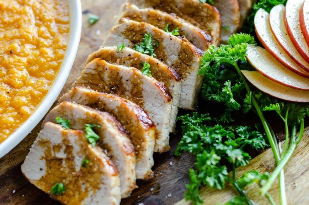 pork tenderloin, sliced, on a cutting board
