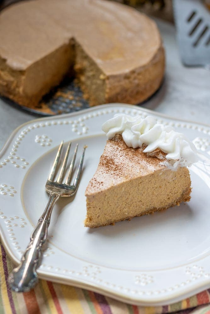 Slice of Pumpkin Cheesecake on plate with fork.