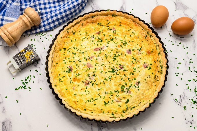 Quiche baked in pie dish topped with chives