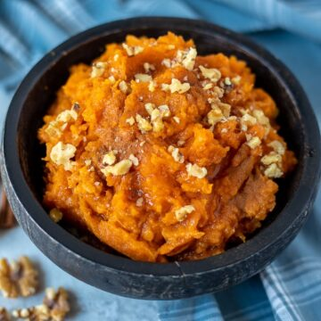 Bowl of Mashed Sweet Potatoes topped with walnuts, maple syrup and cinnamon