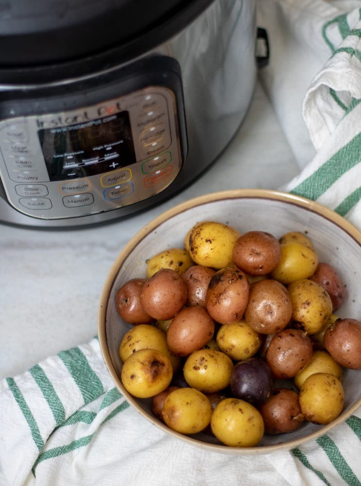 Bowl of Crispy Red Potatoes next to Instant Pot