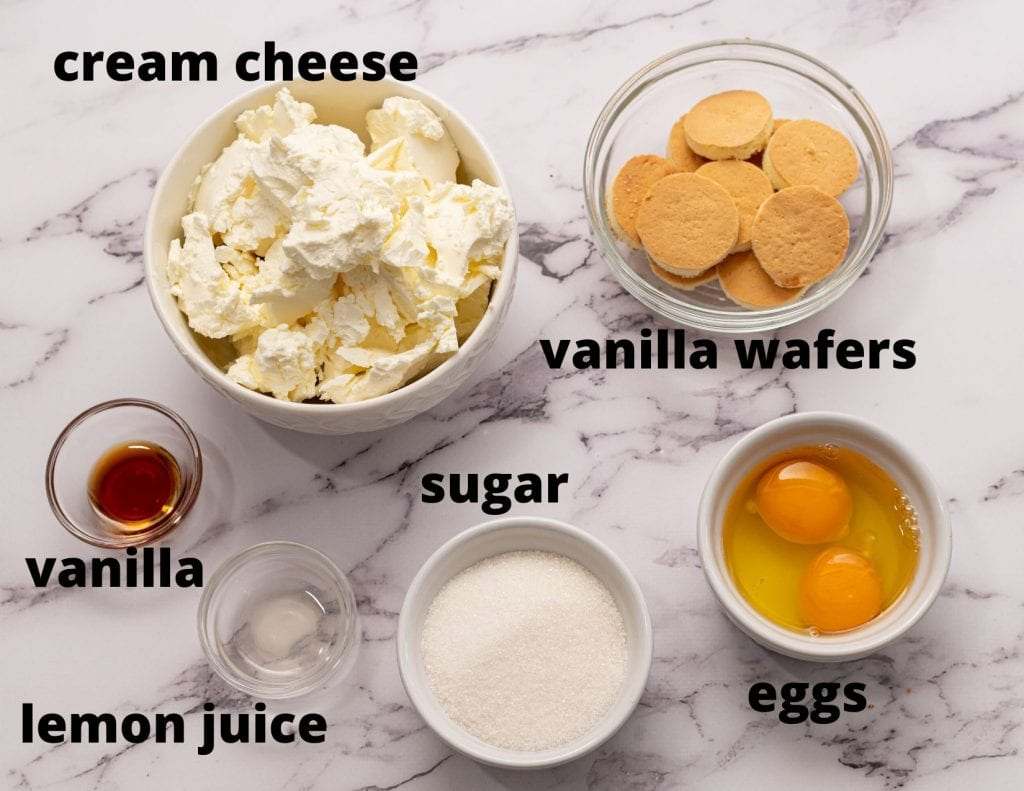 Labled ingredients for cheesecake. Sugar, cream cheese, vanilla, lemon juice, eggs, and vanilla wafer
