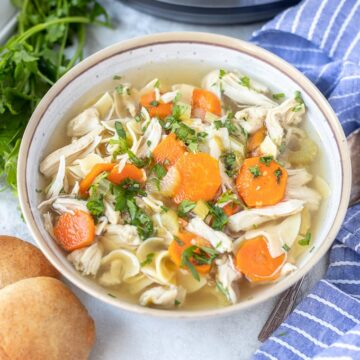Bowl of Instant Pot Chicken Soup next to Instant Pot