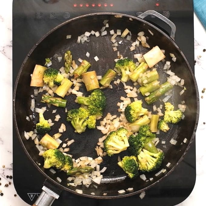 Broccoli, asparagus, and onions being sauteed in cast iron skillet