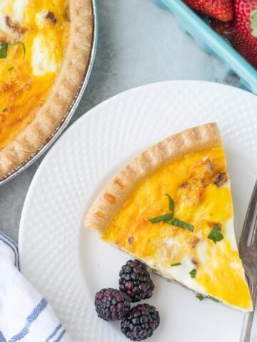 Slice of Quiche with Bacon on white plate