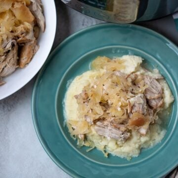Pork and Sauerkraut served on mashed potatoes on blue plate