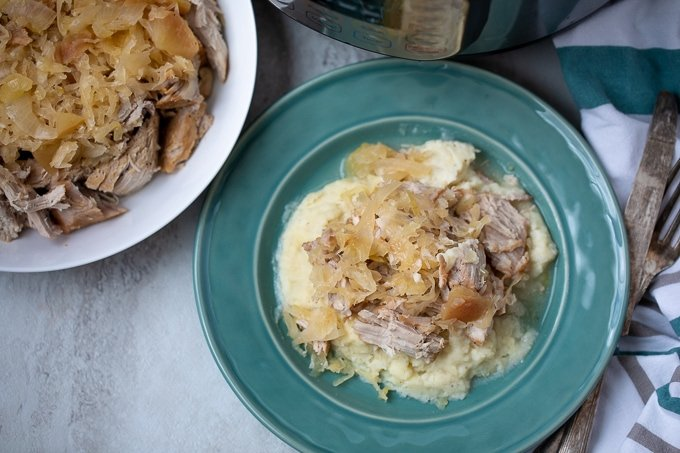 Shredded Pork and Sauerkraut over mashed potatoes on blue plate