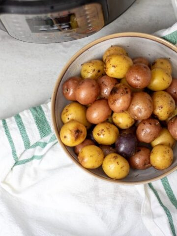 Roasted Garlic Potatoes in serving bowl next to Instant Pot