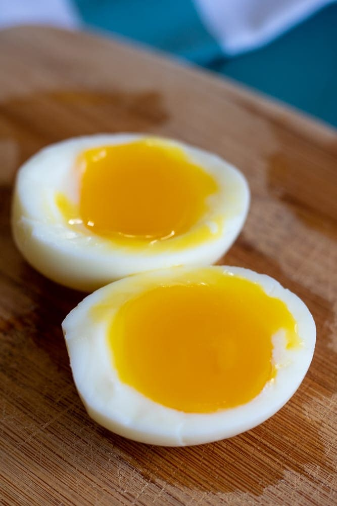 A soft boiled egg cut open on cutting board