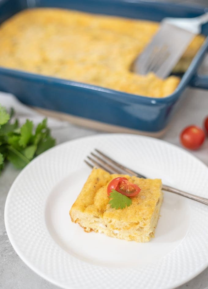 Slice of egg casserole on white plate with diced tomatoes