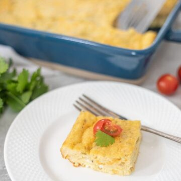 Egg Casserole in Blue Dish with slice of egg casserole on white plate