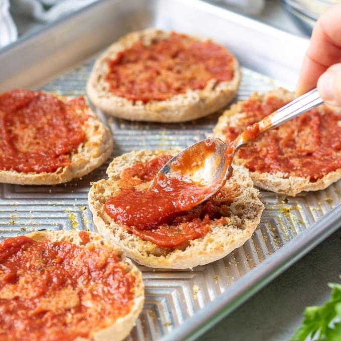 Spreading tomato sauce on english muffins