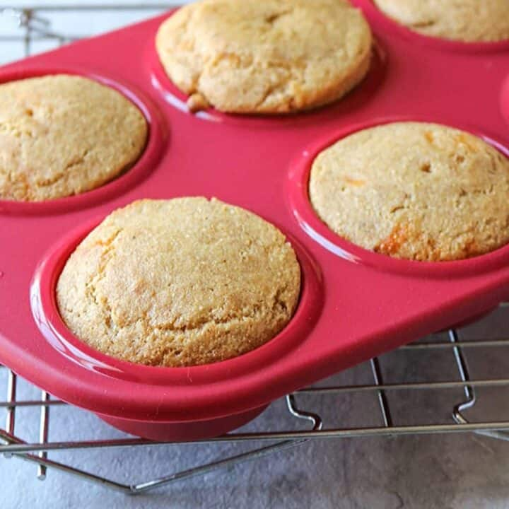 Red muffin tin with corn bread muffins