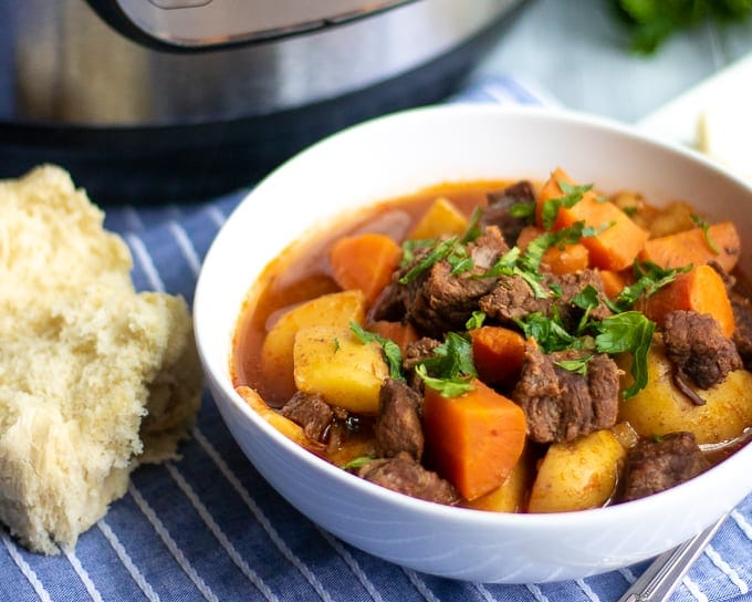 Bowl of Beef Stew with roll on side of bowl with pressure cooker in background.