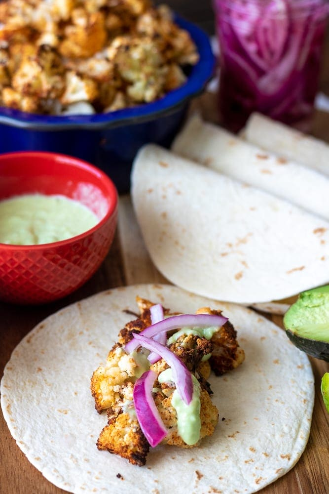 Roasted Cauliflower on flour tortilla with pickled onions and avocado sauce