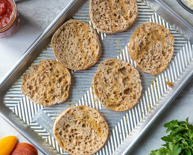 Tray of English Muffin Halves with brushed with garlic oil