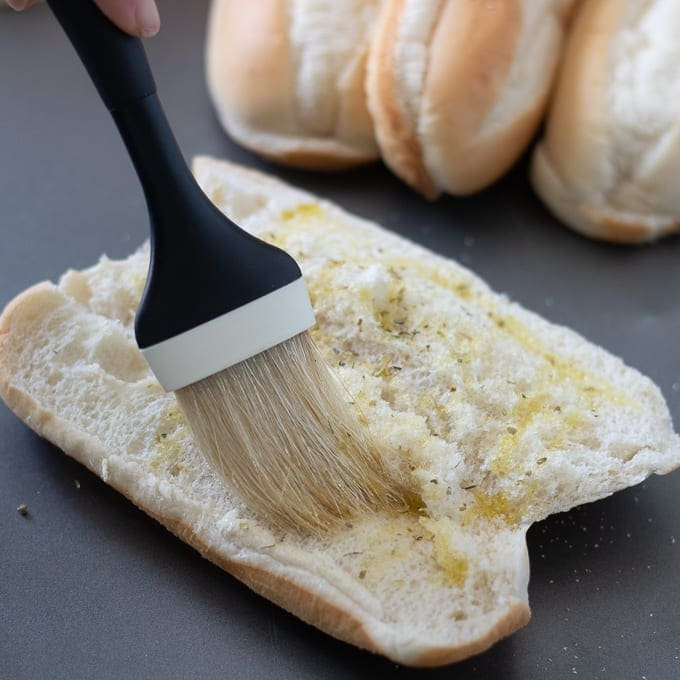 Pastry Brush Brushing Seasoned Olive Oil on Hoagie Bun