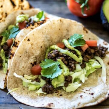 Close up of soft taco filled with lentils with avocado cream