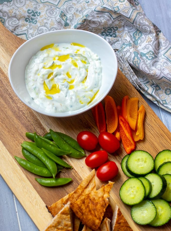 Bowl of Tzatziki Sauce in white bowl on cutting board with fresh veggies and pita bread