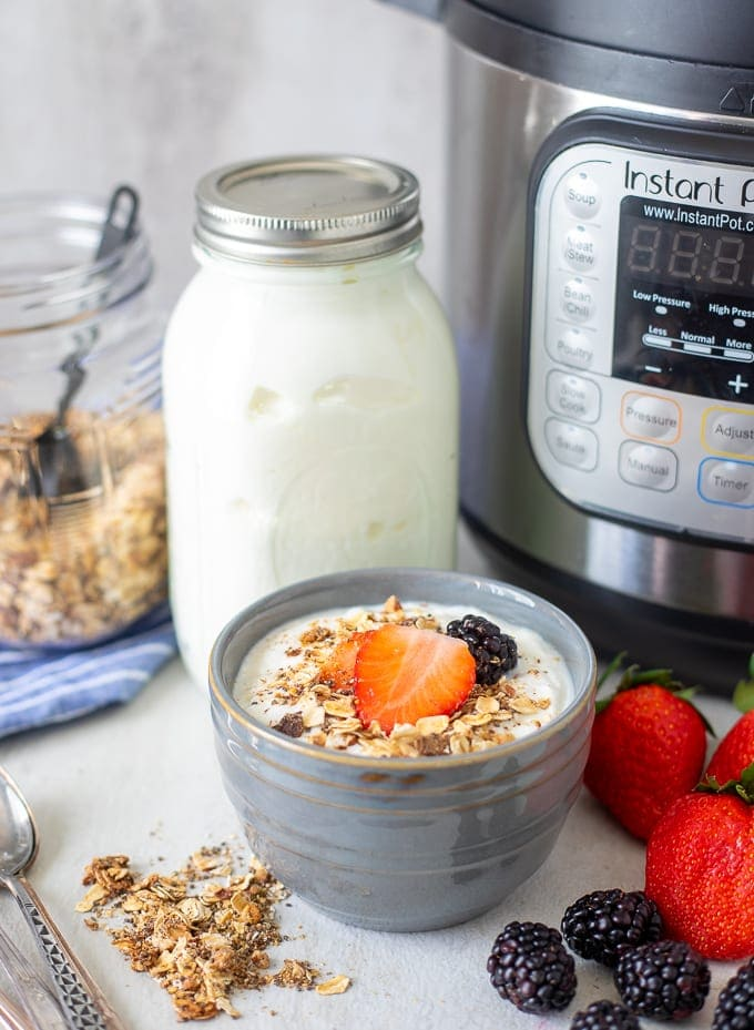 Container of Cold Start Yogurt next to Instant Pot and Bowl of Yogurt topped with granola