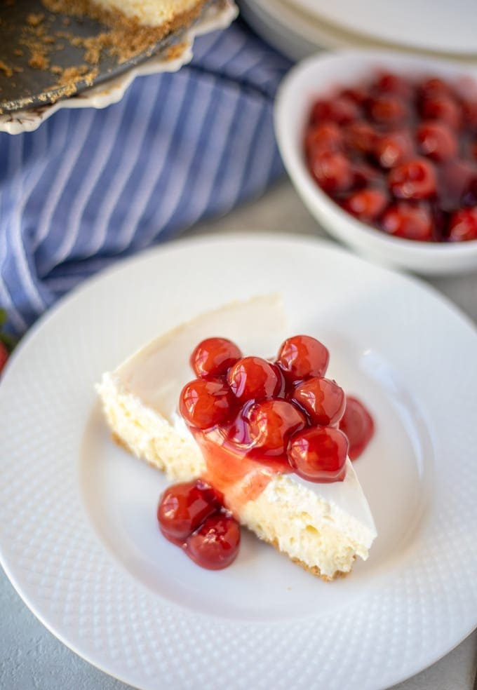 Cheesecake on white plate with cherries on top