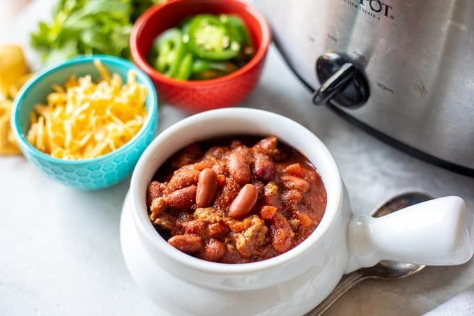 Bowl of crockpot chili next to toppings