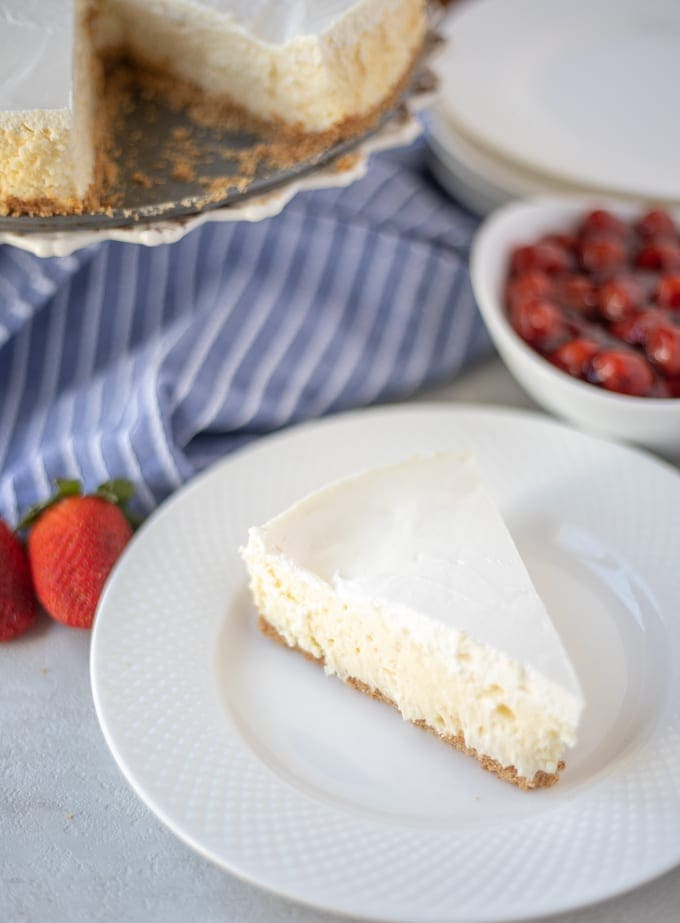 Classic Cheesecake on white plate next to strawberries
