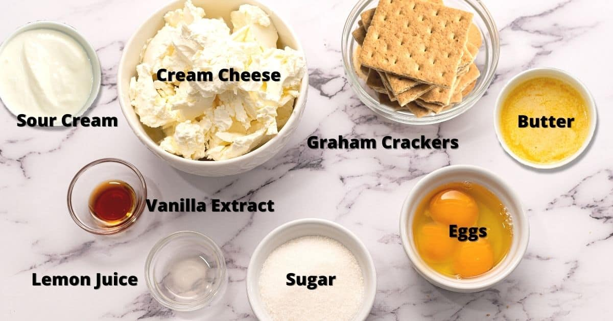 Ingredients for cheesecake labeled on white counter.