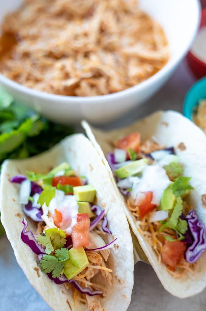 Close up of 2 shredded chicken tacos