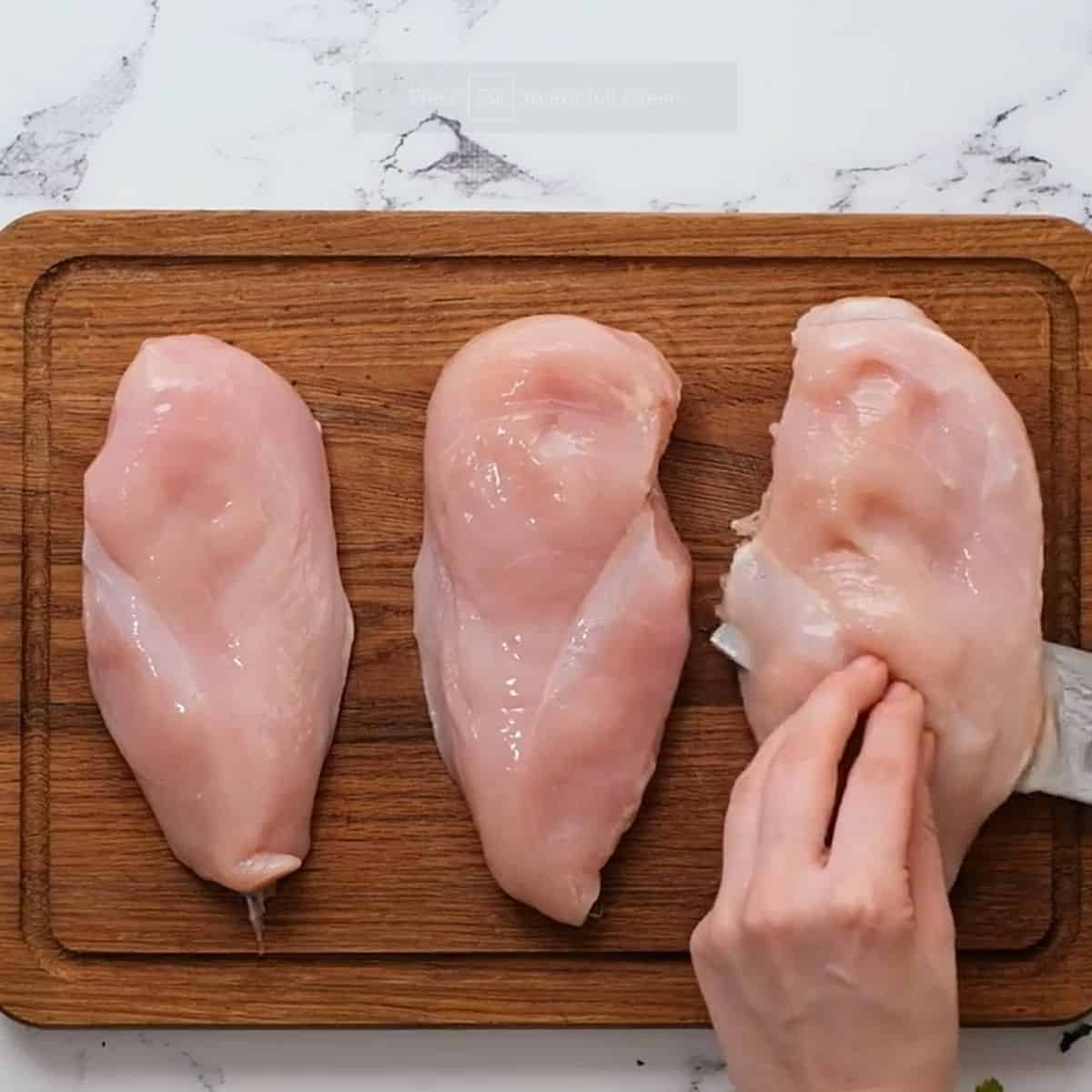 Knife cutting thick chicken breasts into chicken cutlets.