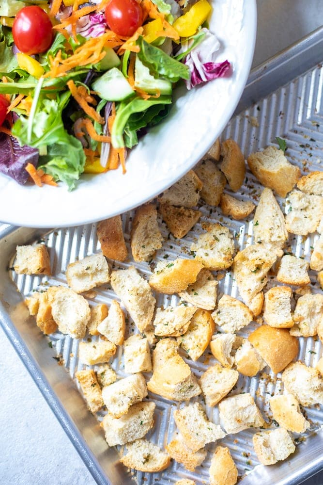 Homemade Croutons on baking sheet next to salad