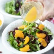 Citrus Dressing being poured over Mandarin Orange Salad