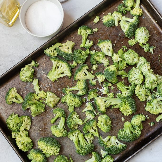 Seasoned Broccoli Spread out on Roasting Pan