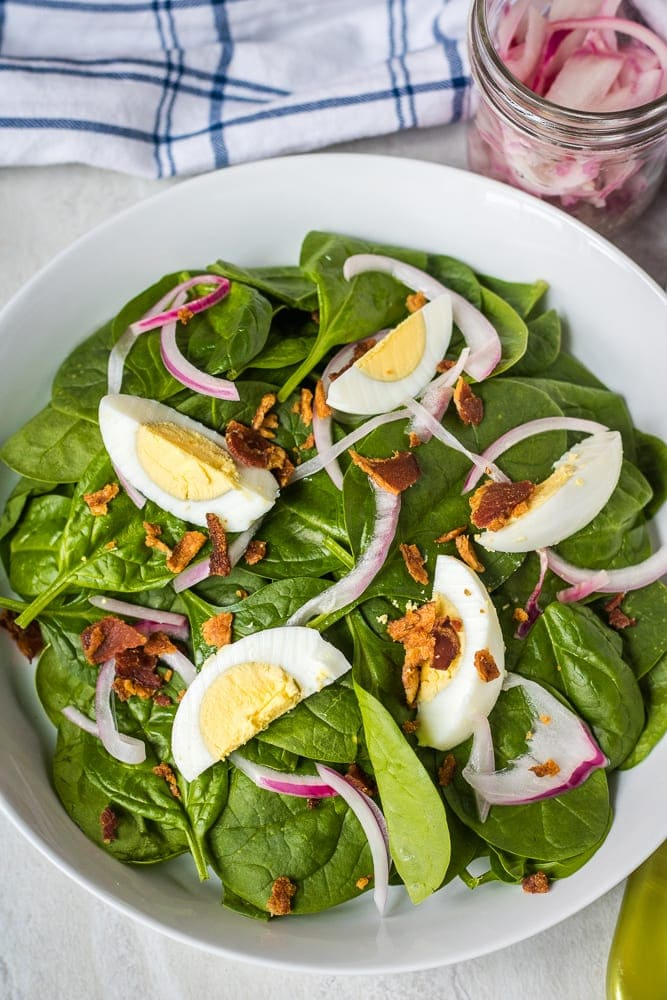 Bowl of spinach salad with hard boiled eggs, bacon and red onions