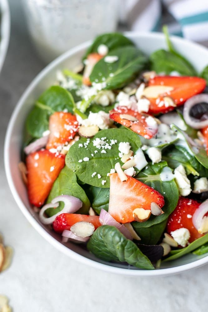 Spinach topped with strawberries, feta, shallots, and almonds