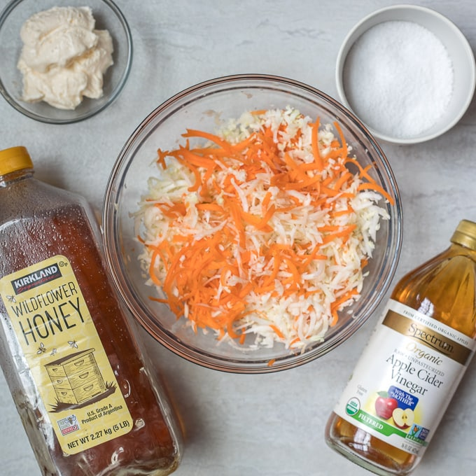 Coleslaw ingredients--cabbage, mayo, salt, honey, and cider vinegar on white counter