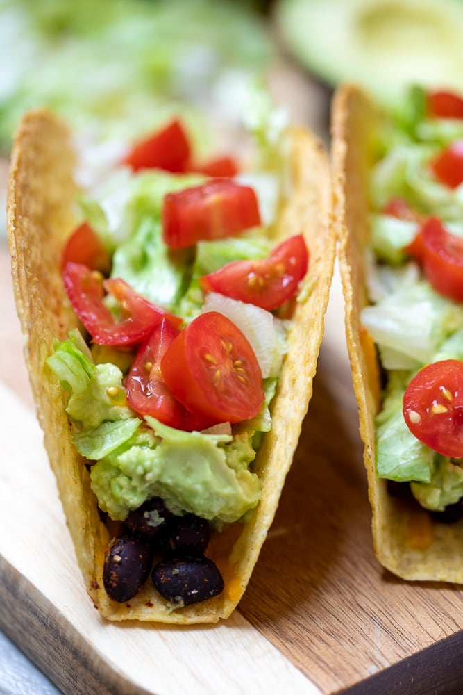 Black Bean Taco on cutting board topped with avocado sauce and tomatoes