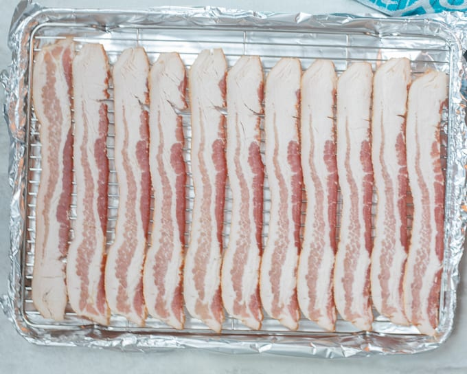 Raw bacon on baking sheet