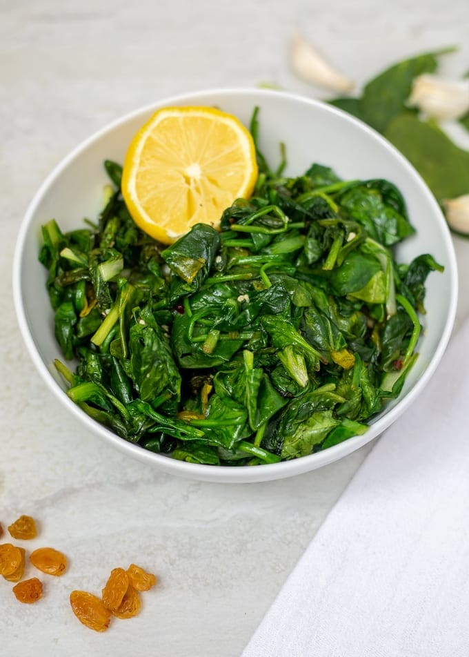 Bowl of wilted spinach with lemon, garlic and raisins
