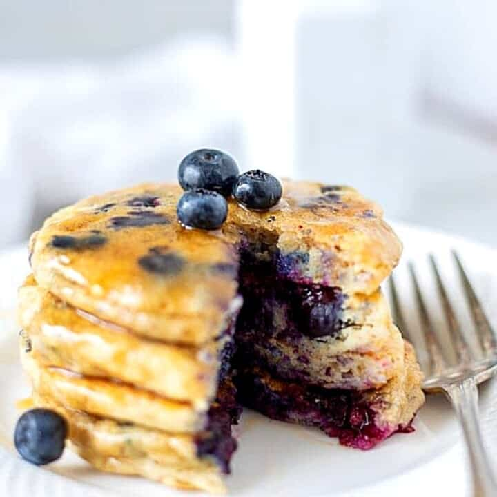 Stack of blueberry pancakes on white plate with fork.