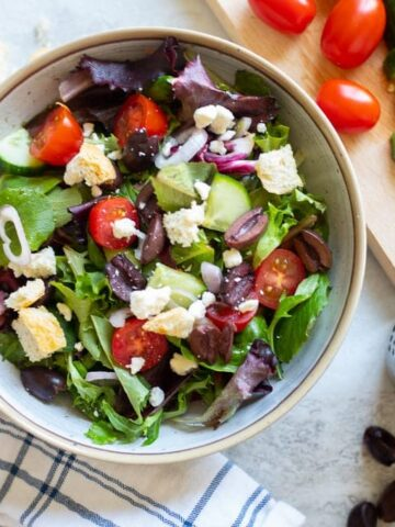 Greek Salad next to cutting board with fresh veggies