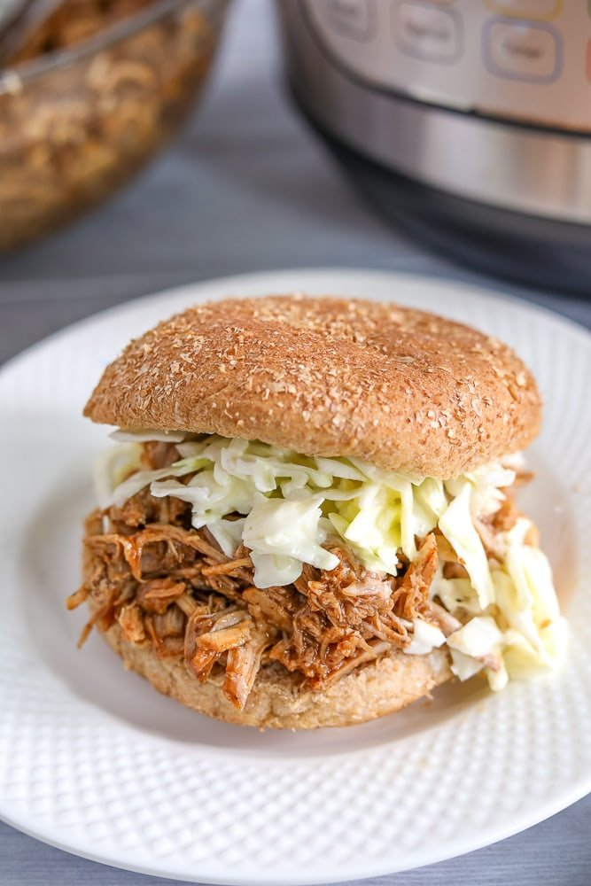 Pulled pork on top of bun topped with apple coleslaw next to Instant pot