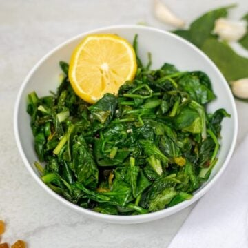 Bowl of wilted sauteed spinach with lemon