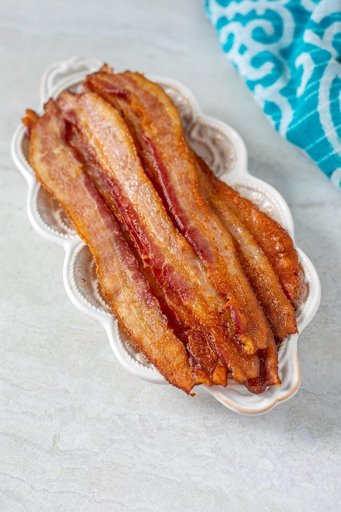 Perfectly baked bacon on white serving platter