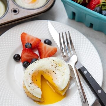 Poached egg cut open to reveal runny yolk on white plate