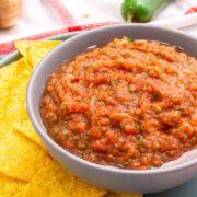 Homemade salasa in gray bowl next to tortilla chips