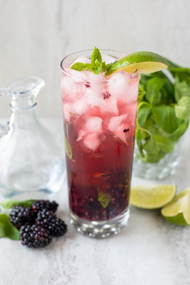 Blackberry Mojito in clear glass with limes and mint