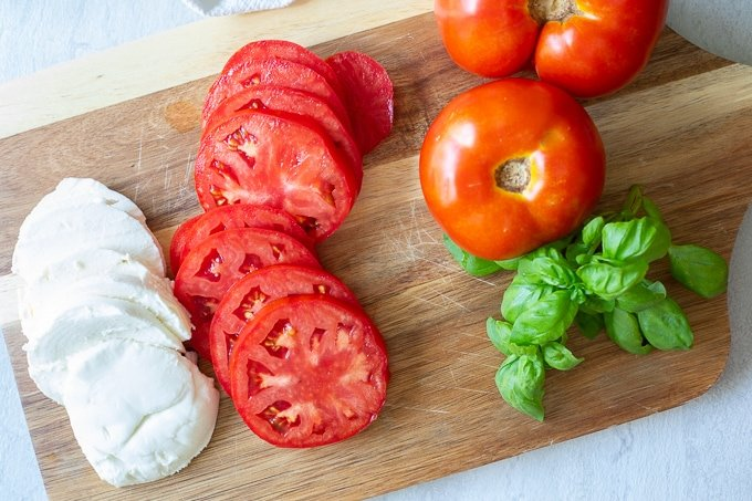Tomatoes, mozzarella and basil on cutting board