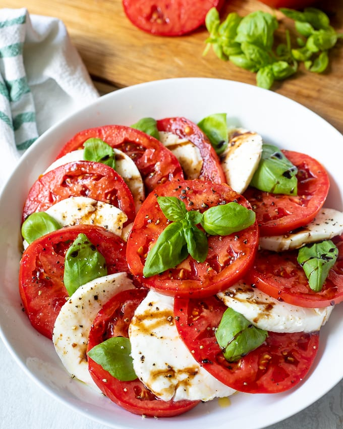 Caprese Salad in white bowl with balsamic glaze